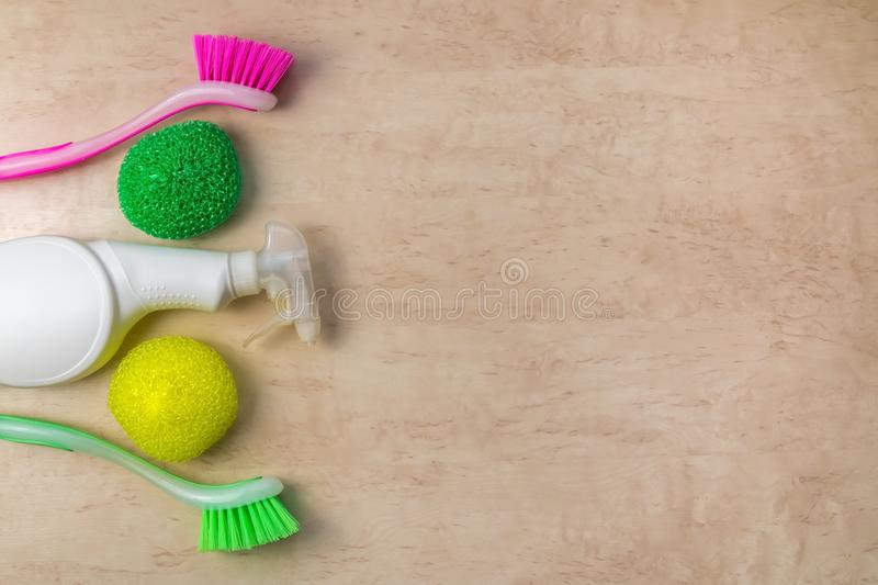 Cleaning supplies and products on wooden background, housework concept, top view with copy space royalty free stock photography