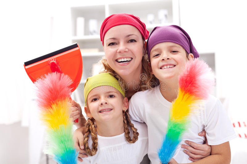 Cleaning taskforce - woman with kids tidy up. Cleaning taskforce - women with kids holding utensils royalty free stock images