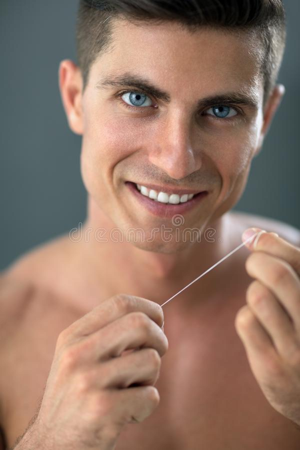 Cleaning teeth with dental floss stock photography