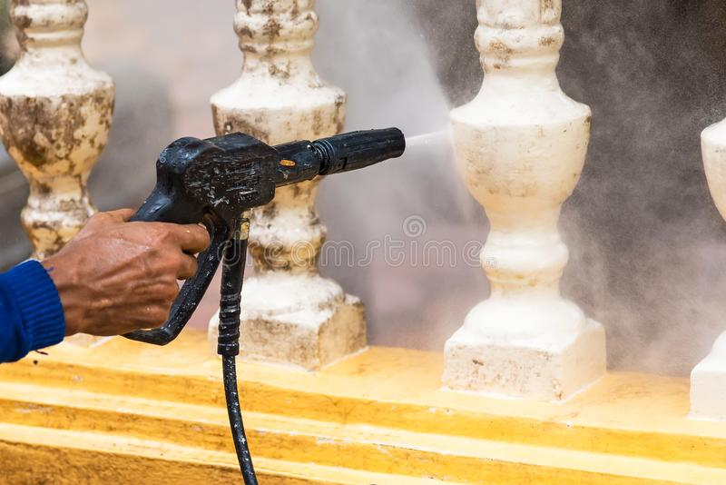 Cleaning terrace with a power washer, high water pressure cleaner on cement terrace surface stock images