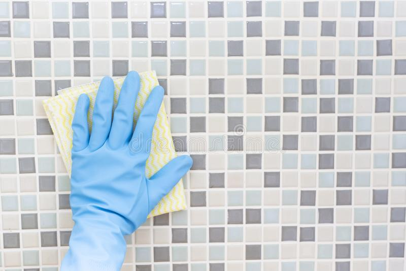 Cleaning tile wall by woman hand with glove, ready to clean house stock photos