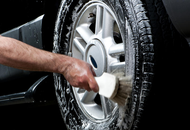 Cleaning tire in a car wash. With brush with hand showing the motion