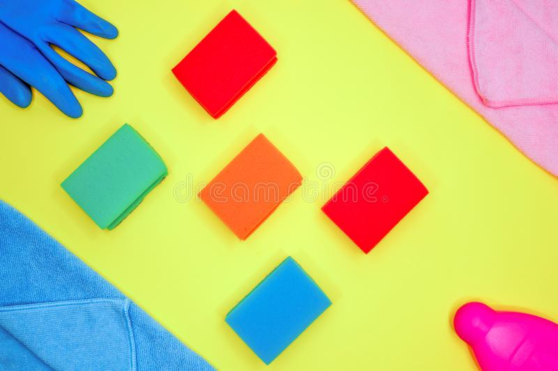Cleaning tools layout. on a yellow background lies a layout of different color sponges, microfiber cloths, rubber glove and stock photos