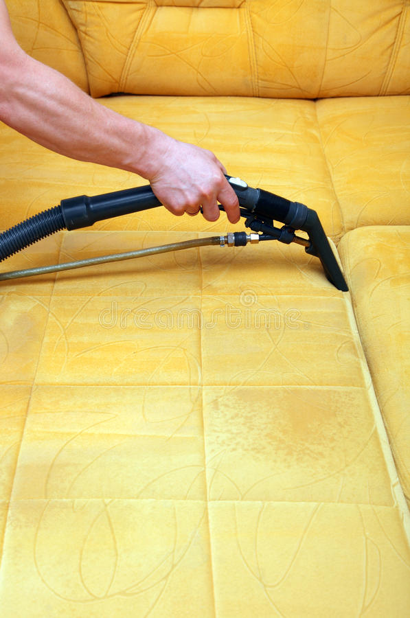Cleaning the upholstery. Man is cleaning the upholstery on the sofa royalty free stock photography