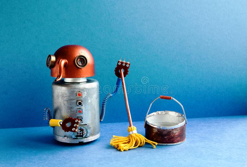 Cleaning washing room service concept. Funny robot janitor cleaner with yellow mop, bucket of water, sweeping floor. Creative design robotic toy cyborg in blue stock photo