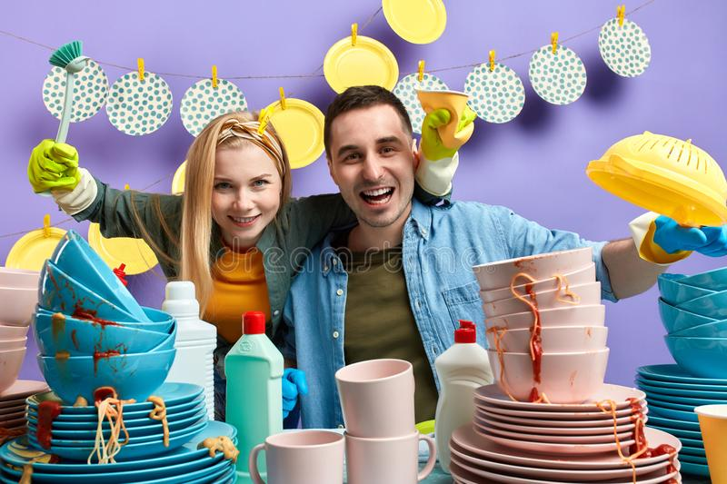 Cheerful happy woman and man standing behind the messy table stock images