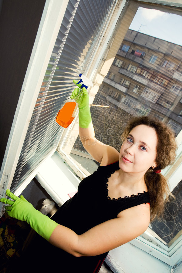 Cleaning window. An image of a woman cleaning the window stock photos