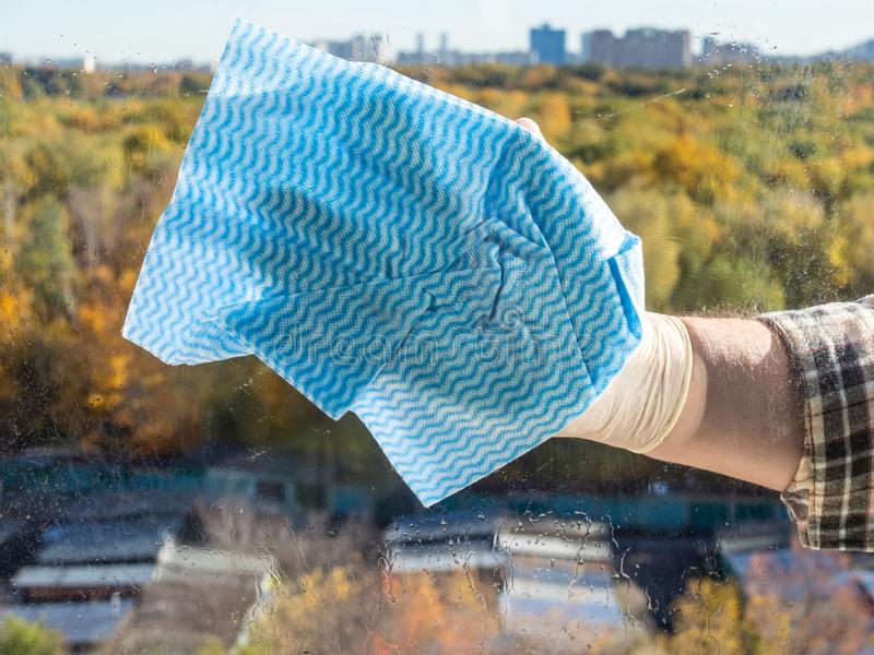 cleaning window glass by blue rag in city royalty free stock photos