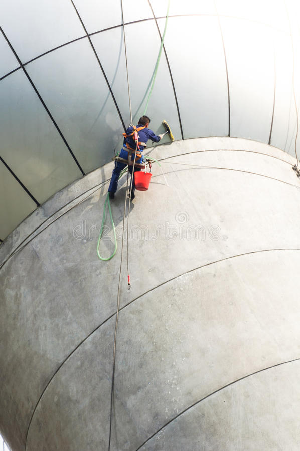 Cleaning windows service on high rise building. it is dangerous. Cleaning windows service on high rise building. The man climber or Spiderman which clean or wipe stock image