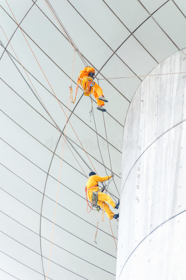 Cleaning windows service on high rise building. it is dangerous. Cleaning windows service on high rise building. The man climber or Spiderman which clean or wipe stock photography