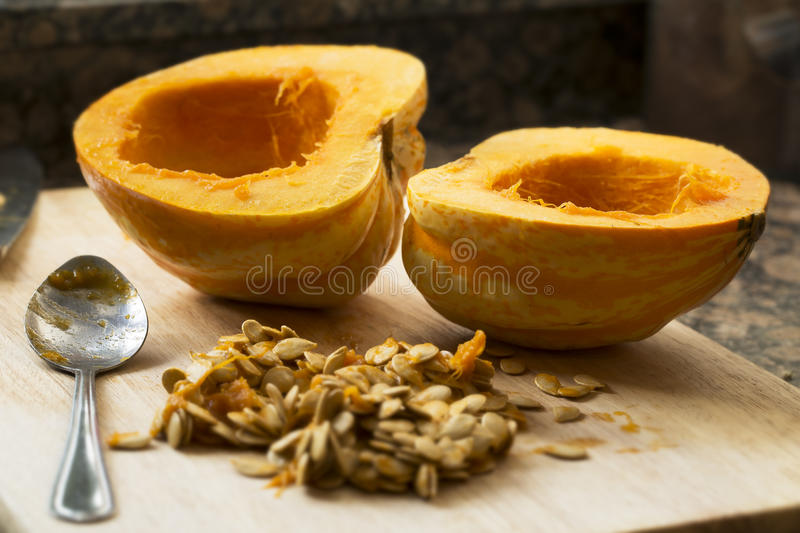 Cleaning Winter Squash. Winter squash cut in half with spoon and seeds scooped out stock image