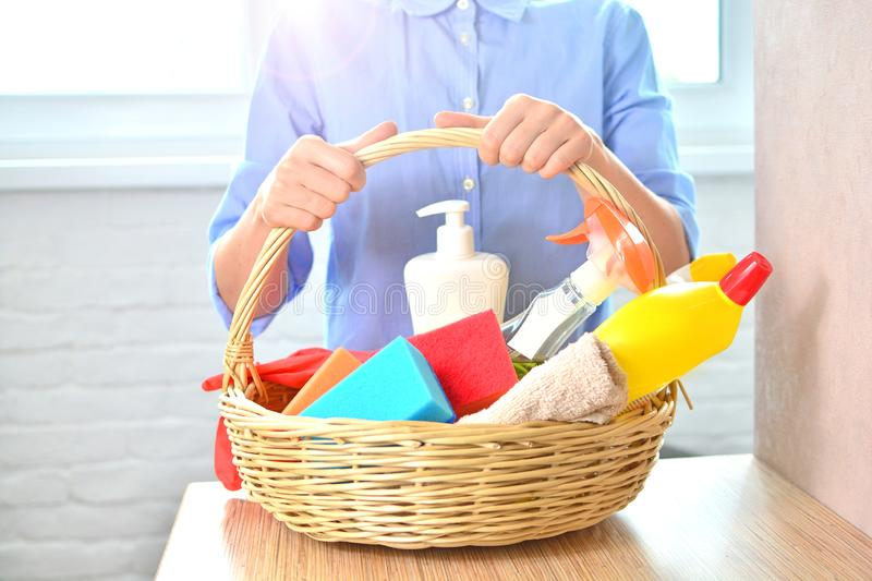 Cleaning woker from service holds a basket with household chemicals stock photography