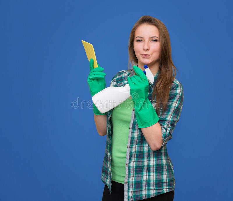 Cleaning woman with cleaning spray bottle happy and smiling. Beautiful cleaning girl isolated on blue background with c royalty free stock photography