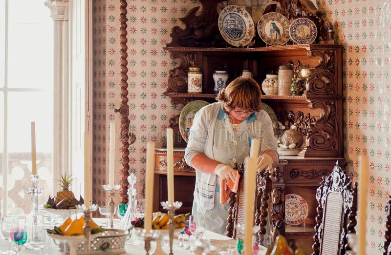 Cleaning woman making nice interior and utensils of dinning room of 19th century Pena Palace royalty free stock photo