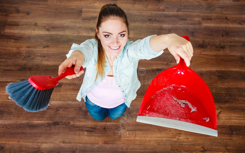 Cleaning woman sweeping wooden floor. Cleanup housework concept. cleaning woman sweeping wooden floor with red small whisk broom and dustpan unusual high angle stock photos