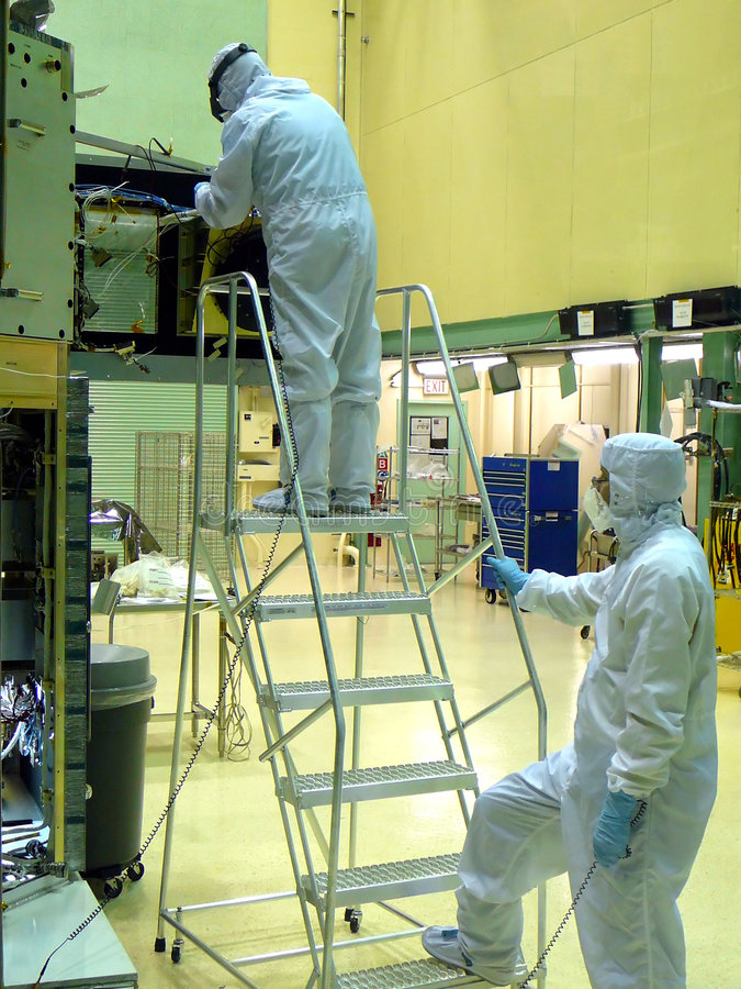 Cleanroom Technicians. Working on high-tech electronics assembly process royalty free stock photo