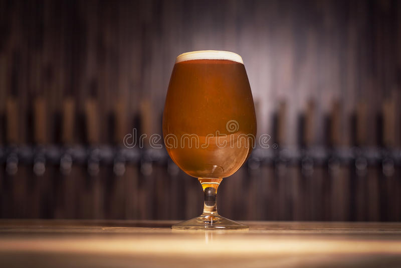 Clear beer with foam on the background of taps royalty free stock photography