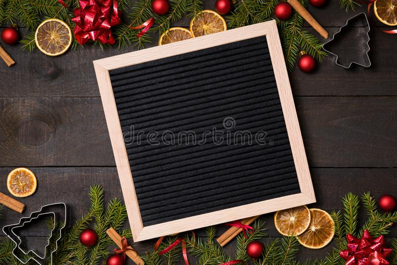 Clear black felt letter board flatlay on dark rustic wood table with Christmas decoration and fir tree boarder. Top view with stock photography