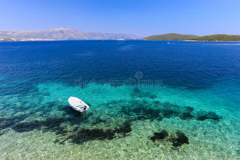 Clear blue beach at Korcula Croatia with boat. And mountain stock photos