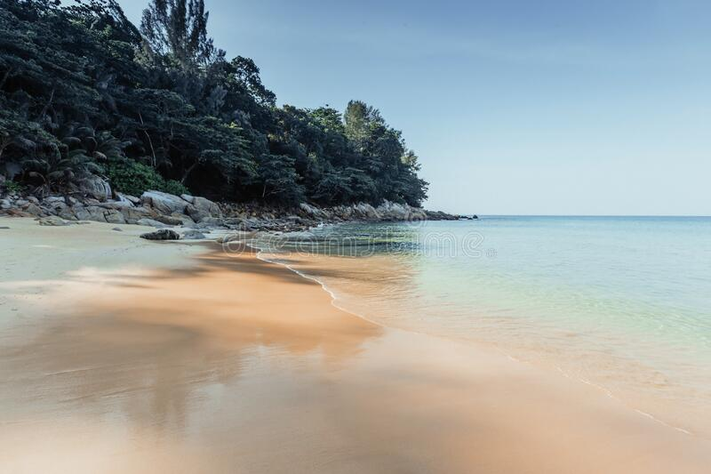 Clear blue sea and beach with palm trees. View from the sea to the Thailand beach, large stones on the shore and clean sand royalty free stock images
