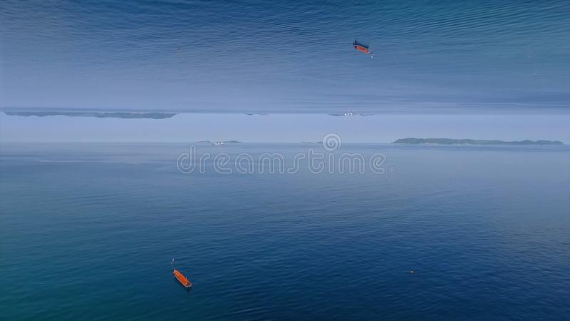 Clear blue sea surface with ripples and lonely red boat, mirror horizon effect. Media. Beautiful calm water of the sea stock photography