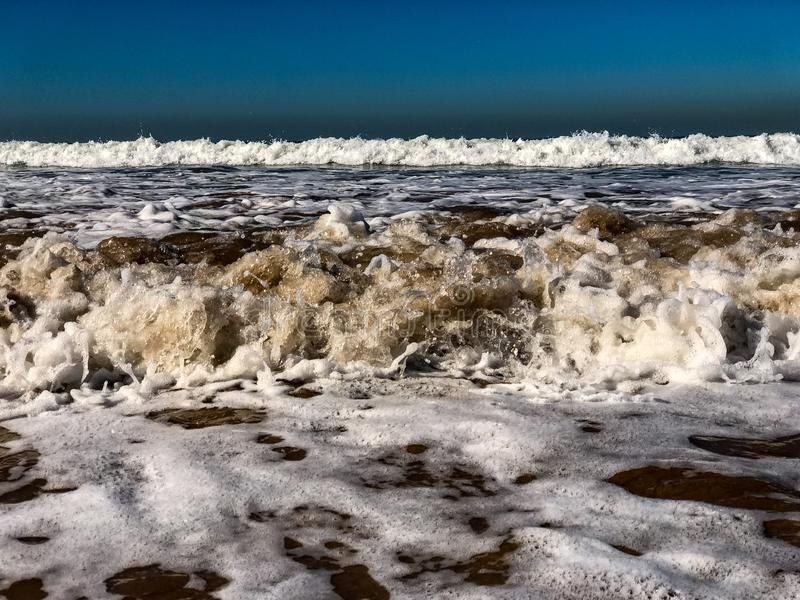 Clear blue skies and sunlight with Atlantic Ocean waves crashing onto sand beach with no people in Agadir, Morocco, Africa stock photography