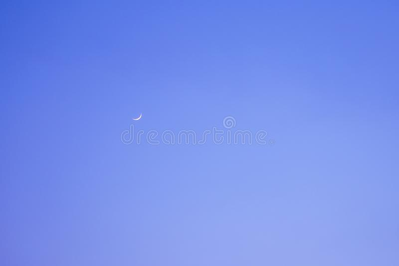 Clear blue sky with shap of moon royalty free stock photo
