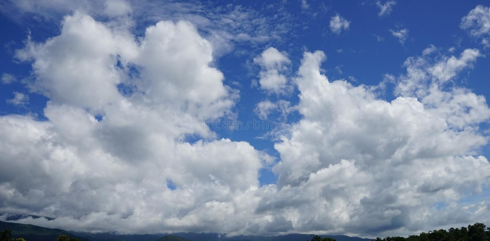 Clear blue sky with soft white clouds stock photo