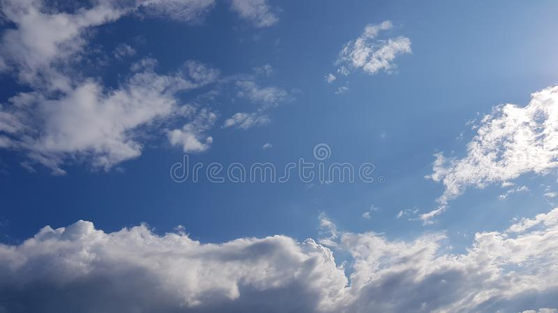 Clear blue sky and white fluffy clouds royalty free stock image