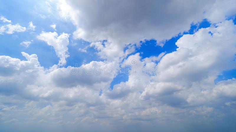 Clear blue sky with white fluffy clouds in summer season at noon time. Abstract nature background stock photography