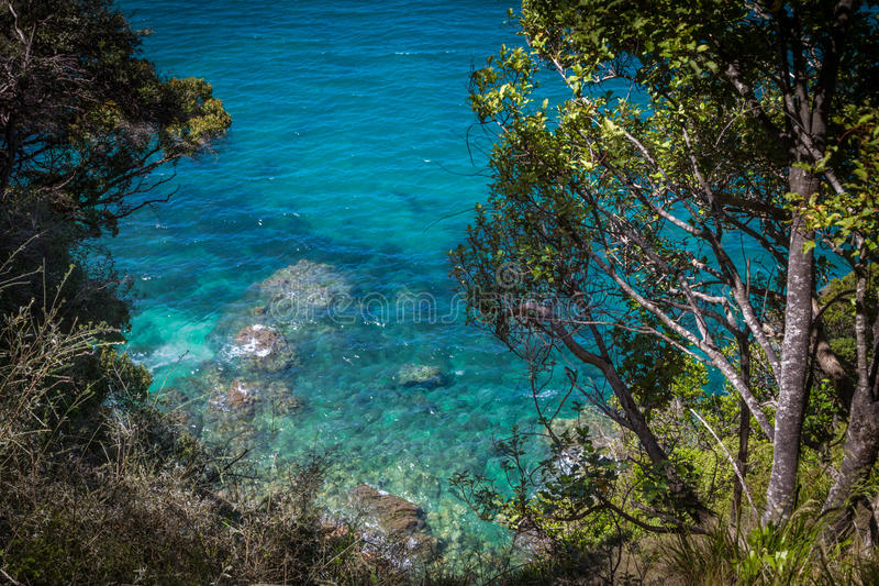 Clear blue waters of ocean and lush greenery in Abel Tasman National Park. New Zealand royalty free stock photography
