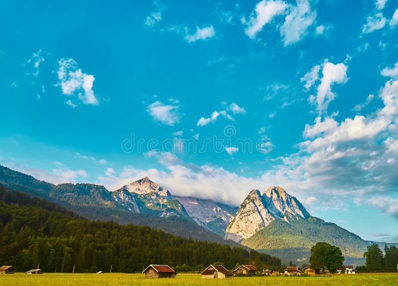 A clear blue-white sky with sun and clouds over the massif of the Bavarian Alps in front of a mountain meadow with a forest and royalty free stock photography