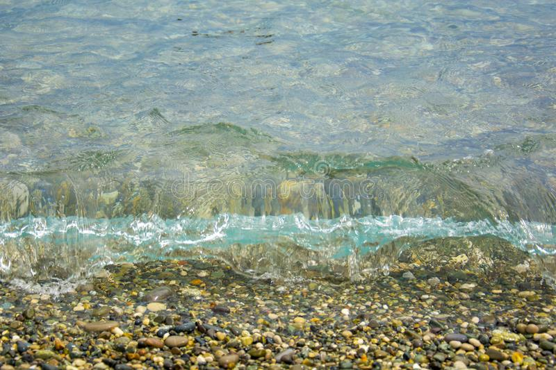 Clear, clean sea wave rolls onto a pebble beach royalty free stock photo