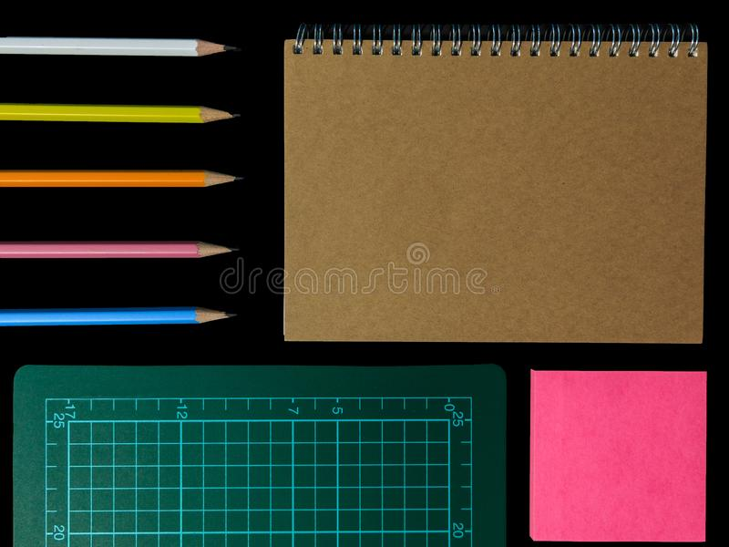 Clear color note book opened for note or lecture note or memo for remine and green cutting mat with black head color pencil in. Clear color note book opened for stock photo