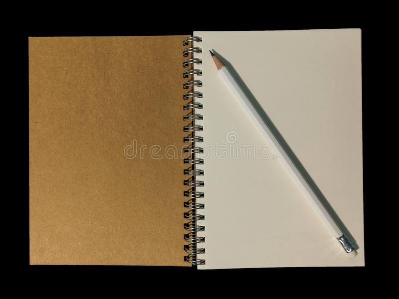 Clear color note book opened for note or lecture note or memo for remine and brown cover whit black head color pencil in white ap. Parel in black background royalty free stock photos