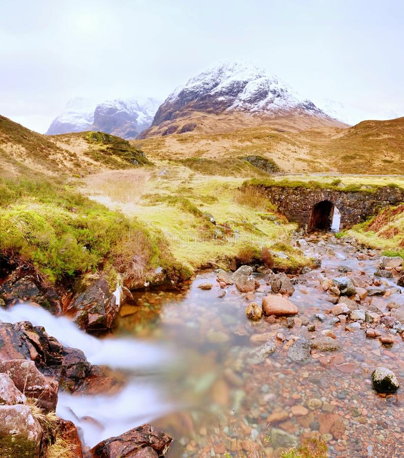 Clear creek stream water flowing over granite stones. Snowy mountains in heavy clouds. In background. Dry grass and heather bushes on stream banks stock image