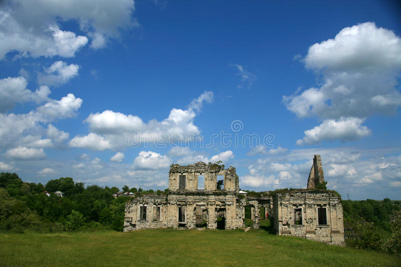 Clear day White clouds An abandoned building made of stone stands in the middle of a steppe valley royalty free stock photography