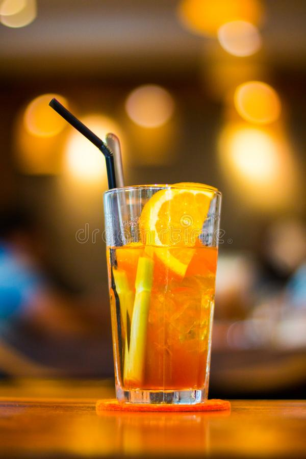 Clear Drinking Glass Filled With Orange Juice With Black Straw royalty free stock images