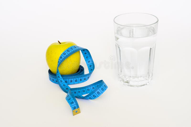 Clear Drinking Glass Near in Blue Tape Measure and Apple Fruit royalty free stock photography