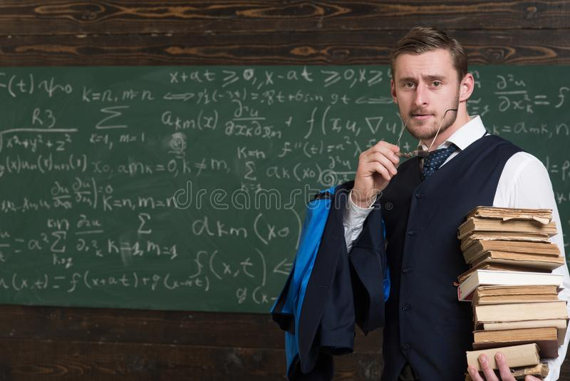 Clear explanation. Teacher formal wear and glasses looks smart, chalkboard background. Chalkboard full of math formulas stock photo