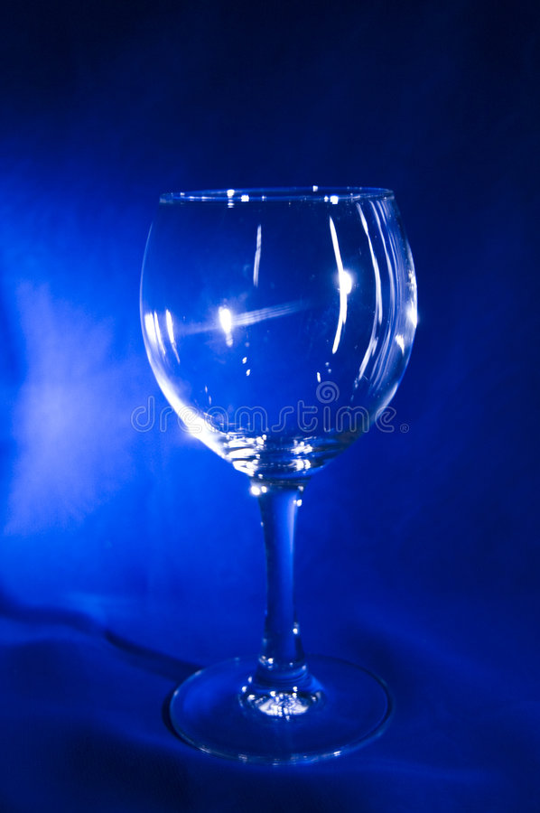 Clear glass on a blue texture royalty free stock images
