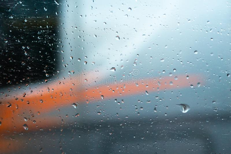Clear glass car with water drops on a blue and orange background. Beautiful texture of rain on the glass stock photo