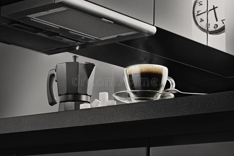 Clear Glcoffee Cup With Black Coffee On Black Kitchen Top Beside Black Coffee Maker