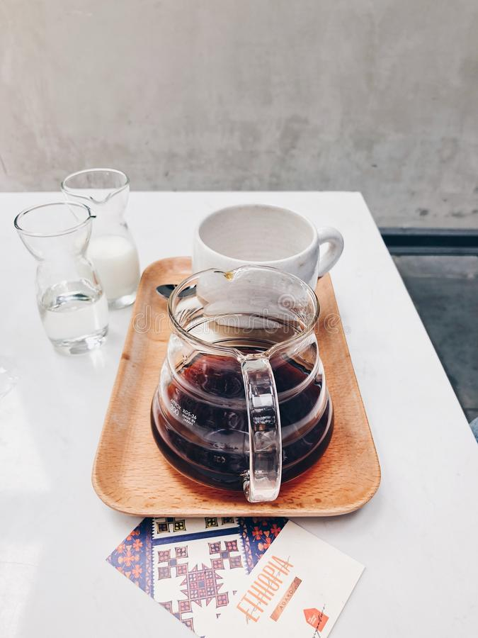 Clear Glass Coffee Pot Near White Mug on Brown Tray stock photography