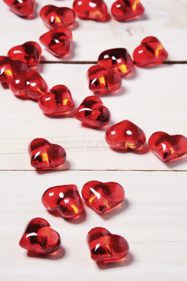 Clear glass effect plastic hearts on a white wooden table. Love, marriage, Valentine concept stock photography