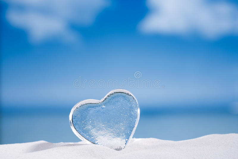 Clear glass heart on white sand beach glitter glass and reflec. Tion , sky and seascape royalty free stock photo