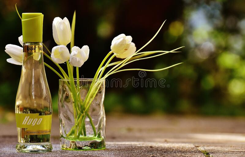 Clear Glass Hugo Bottle With White Flowers royalty free stock images