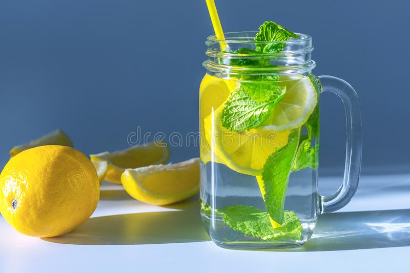 Clear glass mug filled with water, sliced lemon and mint leaves with yellow straw,lit up in the morning light. A close-up photo of a clear glass mug stock images