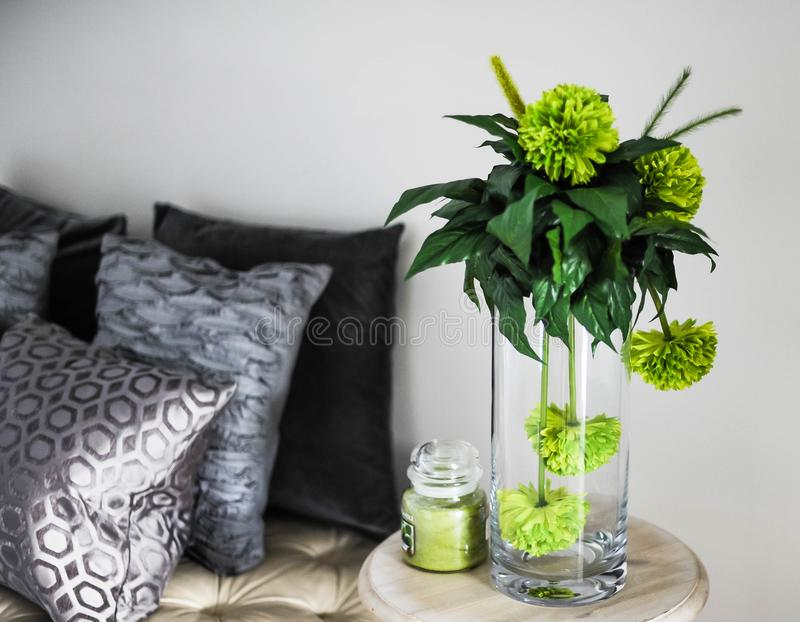 Clear Glass Vase With Green Flowers on Brown Wooden End Table stock photo