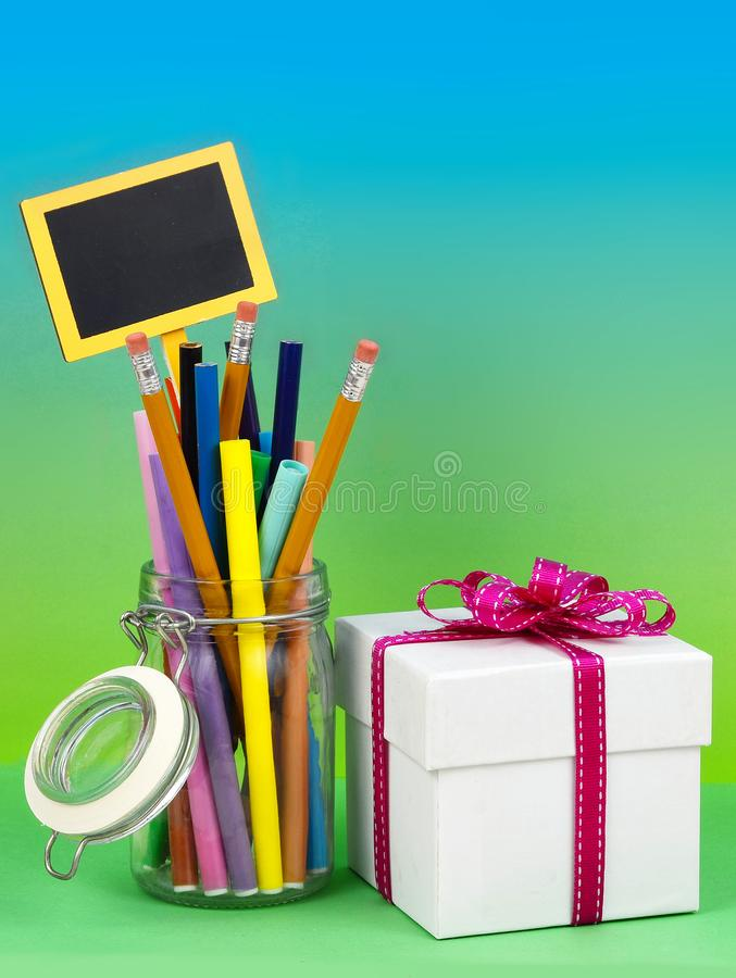 A clear jar filled with colored markers and pencils with a white gift box tied with a pink ribbon on a graduated blue green stock photos
